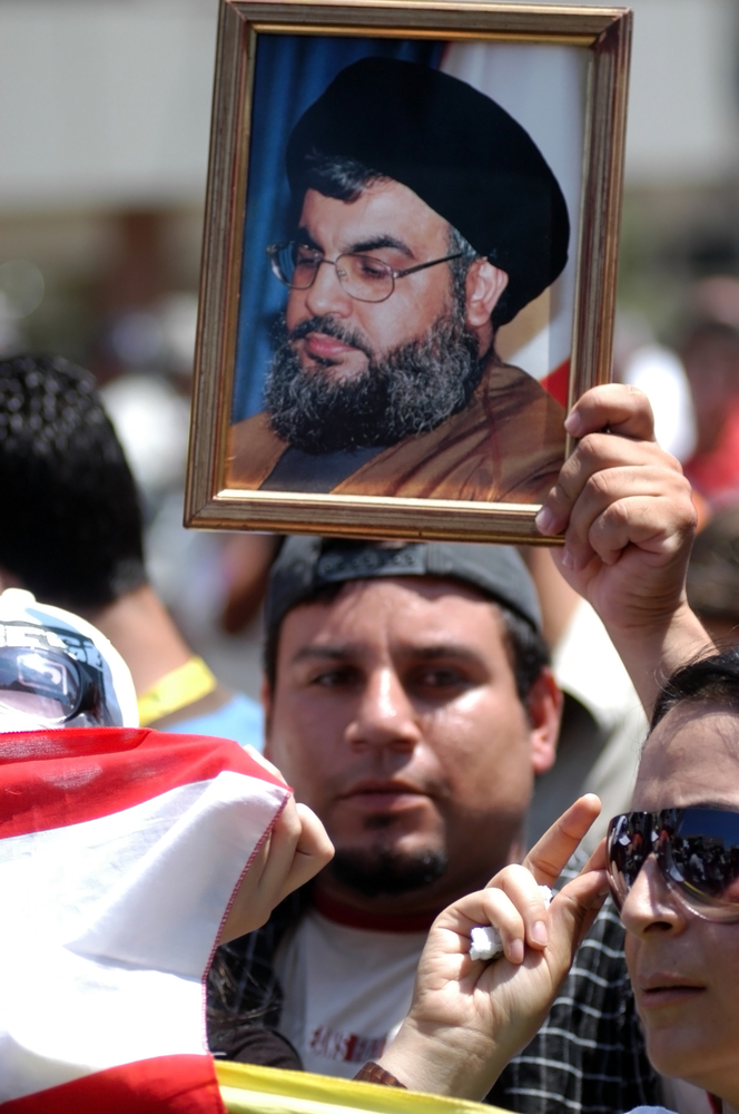 Male protester holds up poster of Nasrallah