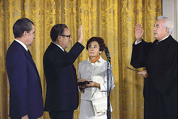 Henry Kissinger sworn in as secretary of State as Nixon looks on and Kissinger's mother holds the bible.